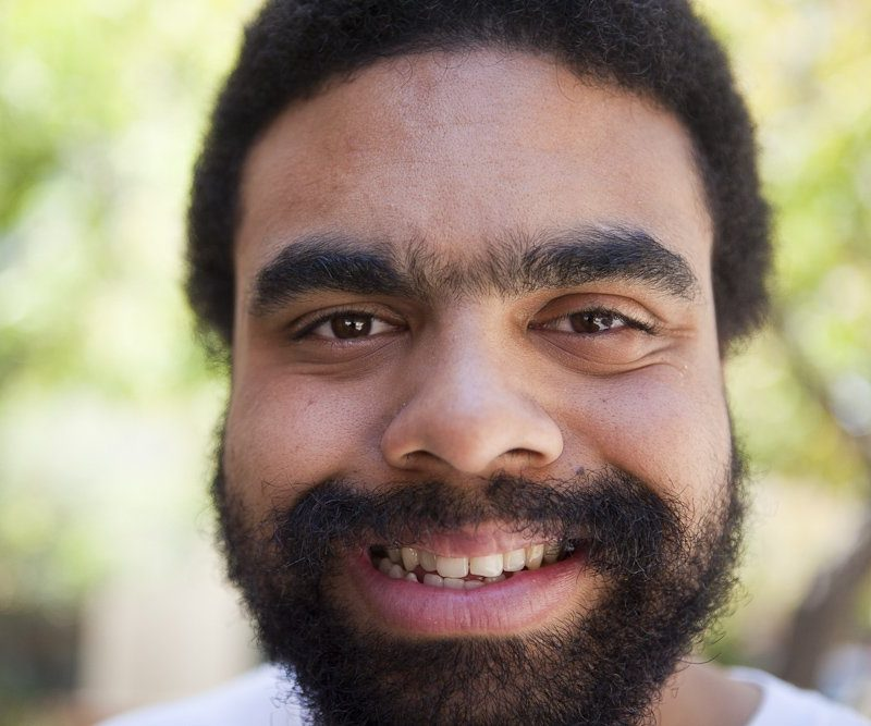 AJ Redmond beams a brilliant smile, looking warmly directly at the viewer. The photo is zoomed in on AJ's face with the background blurred. AJ is a black man in his early 30's with a tight afro and short black beard and mustache.
