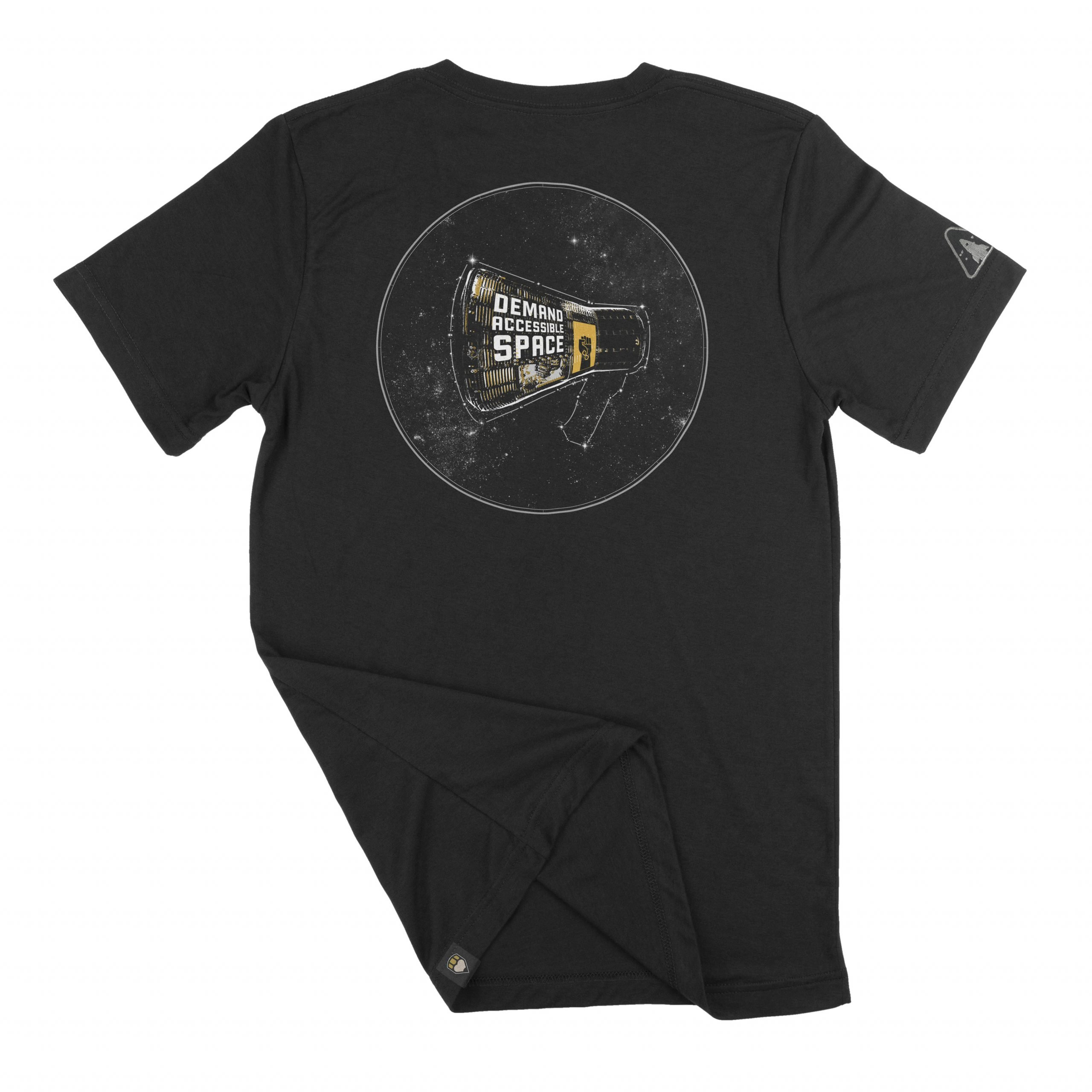 """The back of black t-shirt featuring the """"Rise Up"""" design. The design features a space capsule modeled after the Mercury capsule, depicted in high contrast black and white with gold details, enclosed in a white circle. Wrapping the side of the capsule are the words, """"Demand Accessible Space"""" above a small window. Next to the text and window is a gold banner with a black fist, a gold infinity symbol on the arm of the fist. The banner is a """"Black Disabled Lives Matter"""" graphic created by the same artist. The capsule floats in front of a field of stars, and is outlined by a constellation in the shape of a megaphone."""