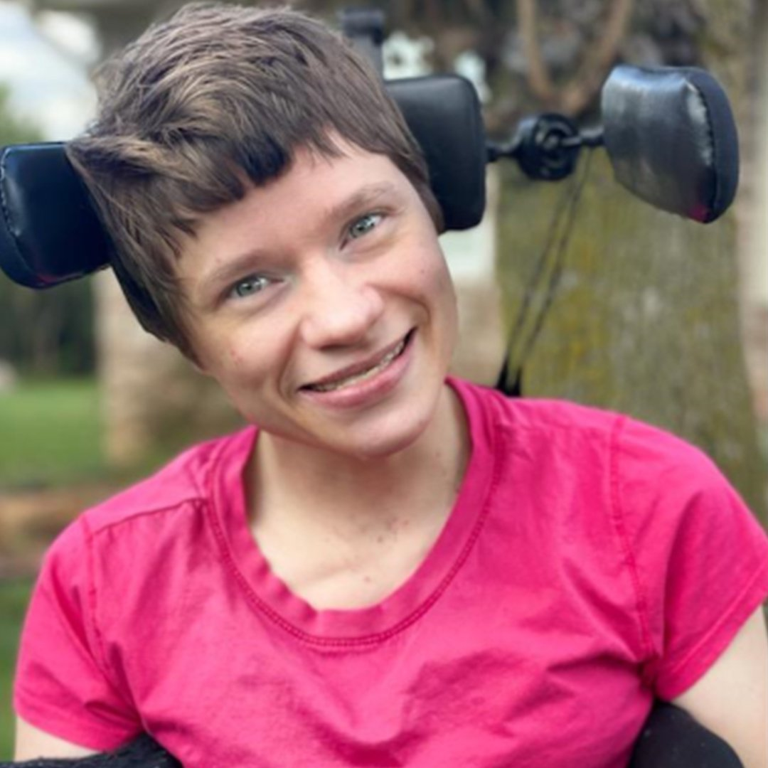 A close up photo of Felicia from the shoulders up. Felicia is a white woman in her early 30's with bright blue eyes, short sandy blonde hair, and a wide friendly smile. She is wearing a bright pink t-shirt. Behind her head the black leather headrest and control array of her power wheelchair is visible. In the distance green grass, two large trees, and blue sky are out of focus.