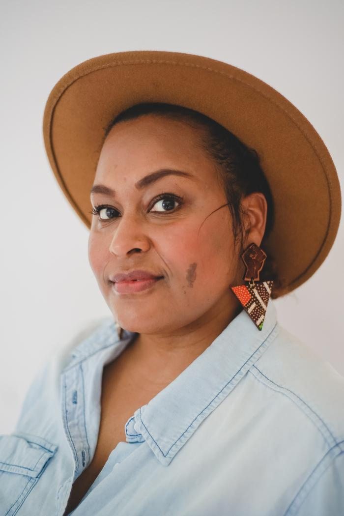 Jen White-Johnson is an Afro-Latina woman wearing a light denim blue button down shirt with the top 4-5 buttons unbuttoned. She's wearing a light tan felt hat and wooden carved ear-rings with the raised fist design above a wooden triangle covered in white, orange, and green strips and dots. She has light brown skin, dark hair pulled back under the hat, a birthmark on her left cheek, dark brown eyes, and smiles slightly at the camera.